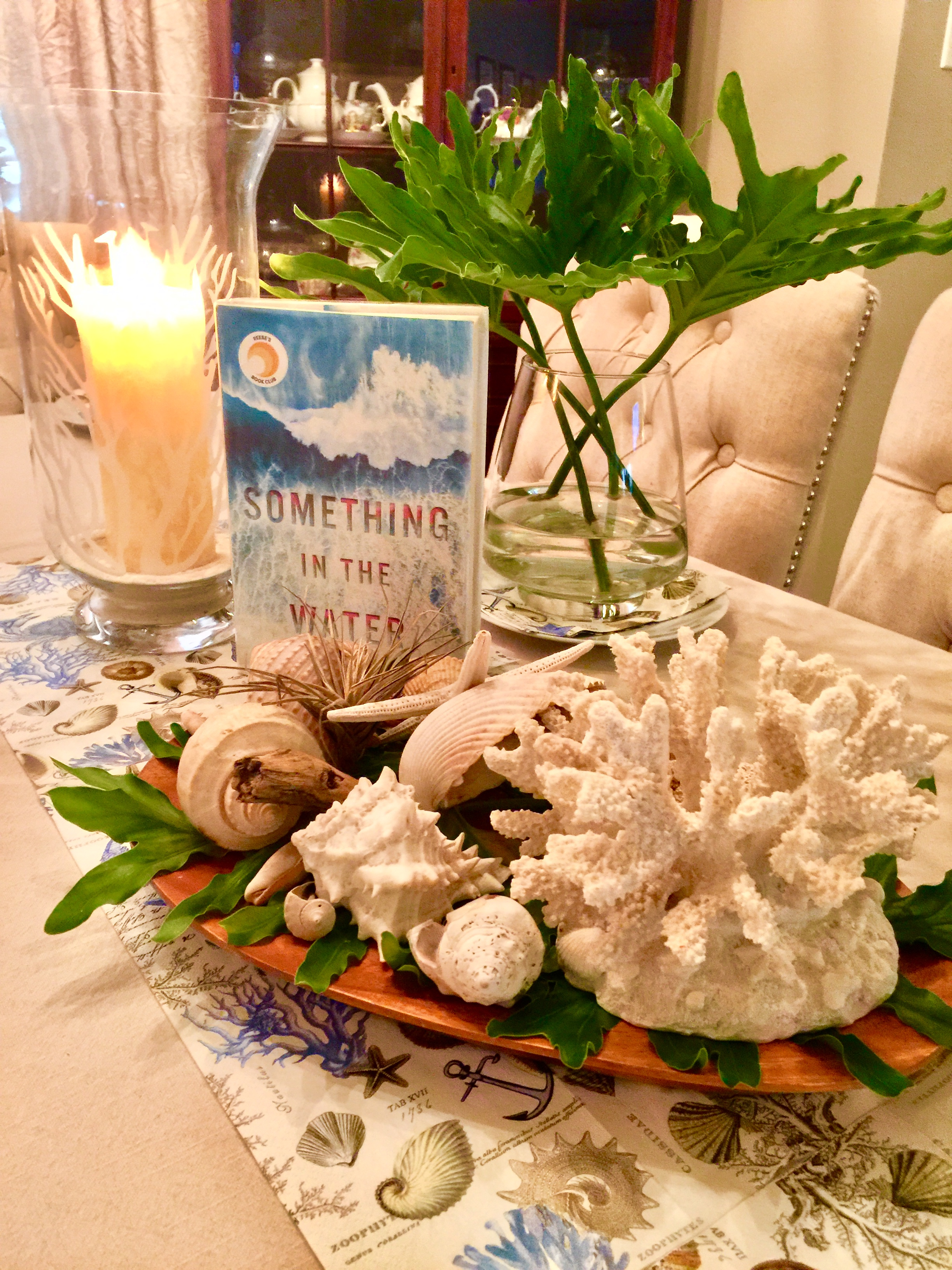 "A newlywed couple finds ""Something In The Water""  while scuba diving in Bora Bora. For the table, paper napkins with seashells, coral and anchors- ironed out and made into a table runner; borrowed shells and coral arranged over tropical green leaves from my yard."