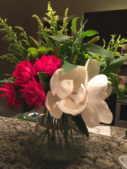 Arrangement composed of knock out roses, a magnolia  and green button mums -  inspired by NOMA's Art In Bloom Exhibit.